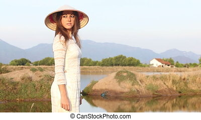 blonde girl in vietnamese costume and hat poses near pond