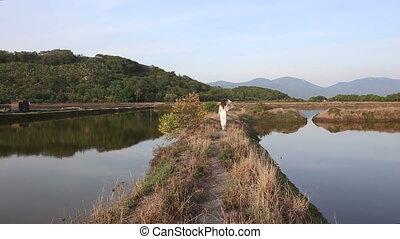 blonde girl in vietnamese costume and hat walks between ponds