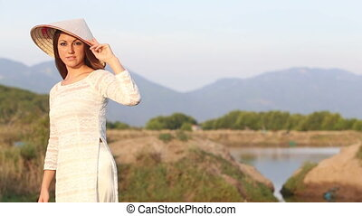 blonde girl in vietnamese dress poses at paddy pond