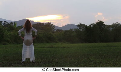 blonde girl in vietnamese dress stands in grass at sunset