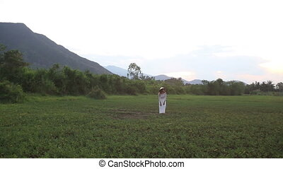 blonde girl in vietnamese poses in valley among mountains