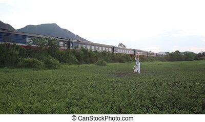 blonde girl in vietnamese poses in valley against train