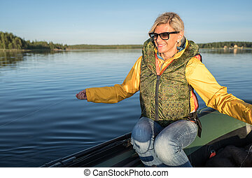 Blonde girl is seating on the boat with fishing line in her hands