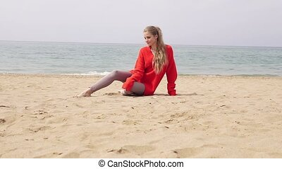 blonde girl is sitting on the sand by the sea and posing for...