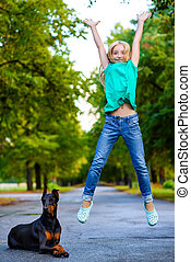 blonde girl jumping near her beloved dog or doberman in summer park