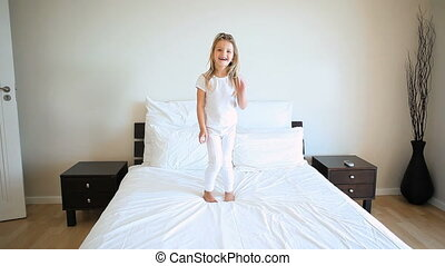 Blonde girl jumping on a bed