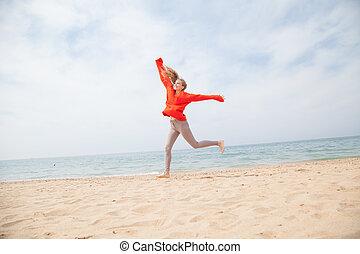 blonde girl jumping on a sandy beach sea shore