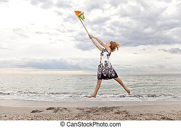 Blonde girl jumping with wind turbine at beach.
