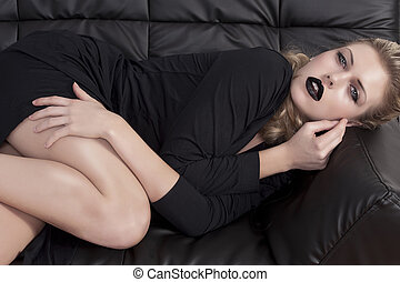 blonde girl laying on a black sofa