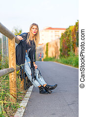 Blonde girl leaning on wooden fence
