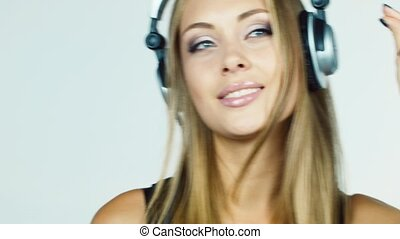 blonde girl listening to music on headphones and dancing...