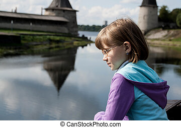 blonde girl looks at the river
