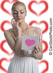 blonde girl looks valentine postcard