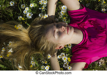 blonde girl lying on flower field with hands behind the head and eyes closed