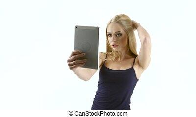 Blonde girl model makes selfie photo on the tablet. Studio