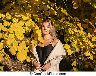 Blonde girl on a background of yellow autumn foliage.