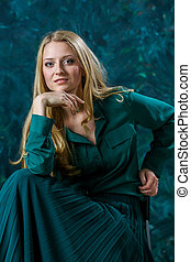 blonde girl on a green background in long dress