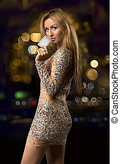 blonde girl on the background bokeh with card for casino