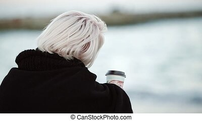 Blonde girl on the beach he drinks coffee Looks intodistance calmly Called her Looks at the camera