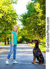 blonde girl playing with the dog or doberman in summer park