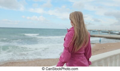 Blonde girl raises her arms up on the beach