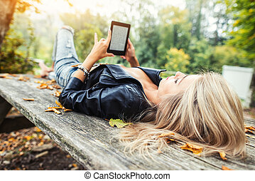 Blonde girl read ebook lying on wooden table in autumn park