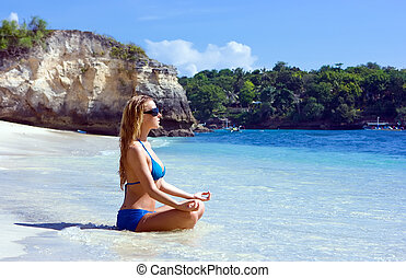 Blonde girl relaxing in water on the beach