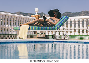 Blonde girl relaxing poolside reading - Young lady on sun...