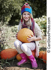 Blonde girl resting in the field full of pumpkins