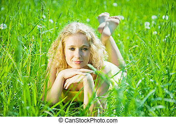 blonde girl rests on grass