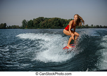 Blonde girl riding on the red wakeboard