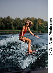 Blonde girl riding on the red wakeboard on the lake