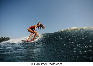 Blonde girl riding on the wakeboard on the lake