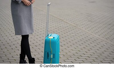 Blonde girl rolls a suitcase near the airport terminal