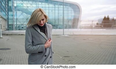 Blonde girl rolls a suitcase near the airport terminal. Slow...
