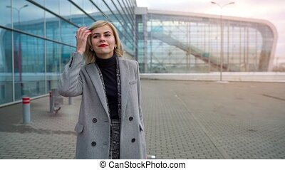 Blonde girl rolls a suitcase near the airport terminal. Slow motion