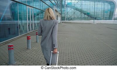 Blonde girl rolls a suitcase near the airport terminal - view from the back