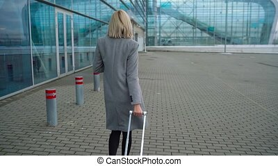 Blonde girl rolls a suitcase near the airport terminal - view from the back. Slow motion