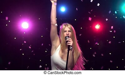 Blonde girl singing and dancing with retro microphone. Slow motion