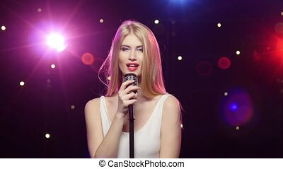 Blonde girl singing into a retro microphone strobe lighting effect