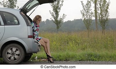 blonde girl sits in open trunk of her broken car with...