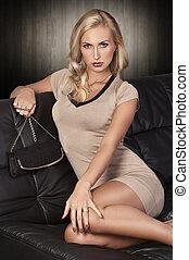 blonde girl sitting on a black sofa