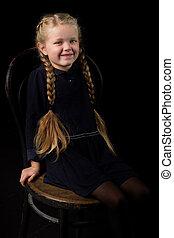 Blonde girl sitting on chair in dark room