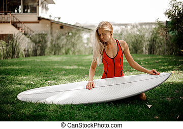 Blonde girl sitting on her knees holding the wakeboard