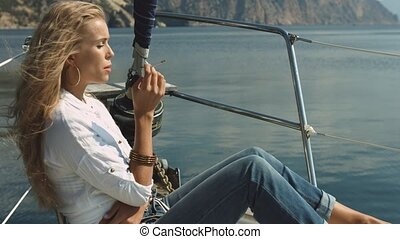 Blonde girl smokes on the yacht