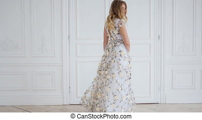 blonde girl spinning in a long dress