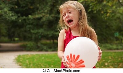blonde girl stand with balloon in hands and cries