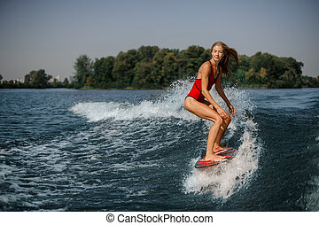 Blonde girl standing on the red wakeboard