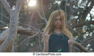 blonde girl straightens her hair in the wind