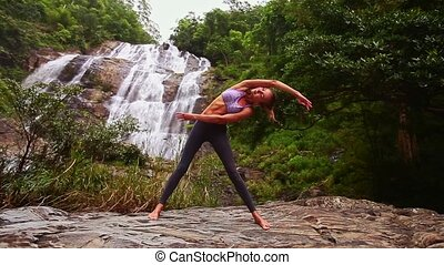 Blonde Girl Stretches among Jungle against Beautiful Waterfall